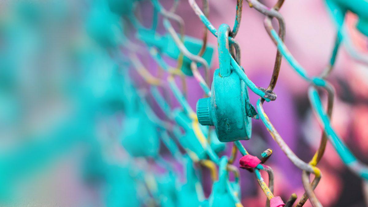 Locked padlock on a fence