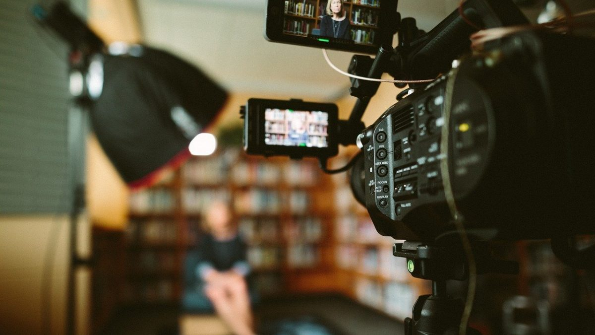 Video camera filming a person in a library. The person is out of focus.