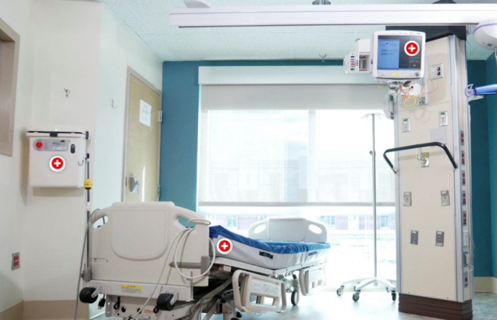 An image of a hospital room hotspots over the bed, monitor and wall for students to click on for more information.