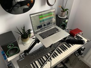 Chris's home music studio, a laptop sits above a digital keyboard. There's a guitar on the wall and pot plants on the speakers