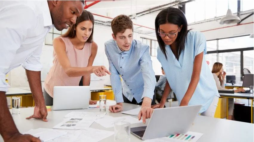 Group of people working together around a laptop