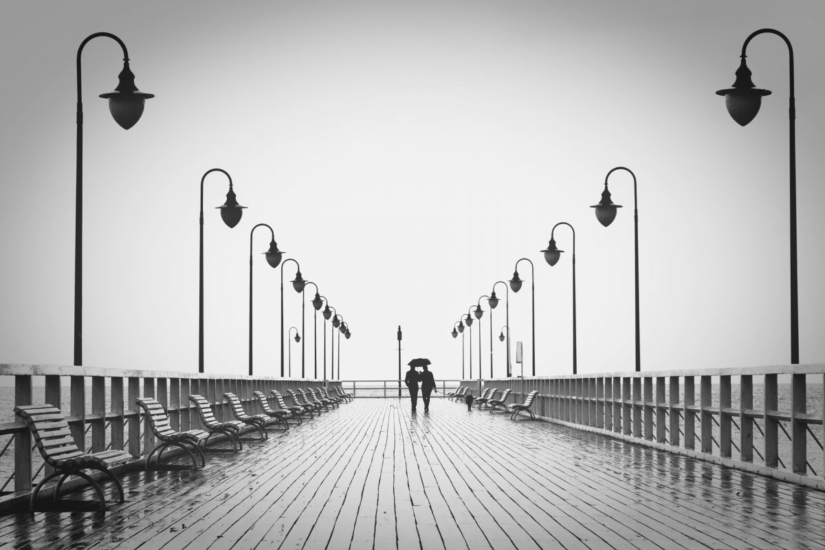 2 people walking down a pier at the seaside. Black and white image.