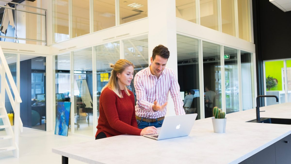 Man and woman discussing in a modern, open plan office
