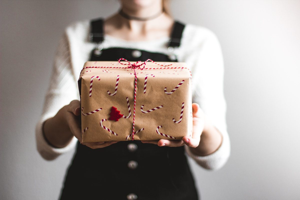 Image of woman holding out a gift-wrapped box